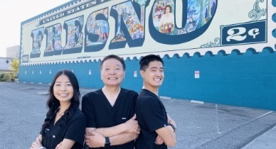 Three dentists with Fresno mural