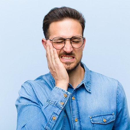Man with glasses in need of an emergency dentist