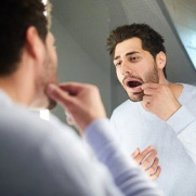 man looking at his mouth in the mirror