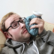 man lying on a couch and holding an ice pack to his cheek