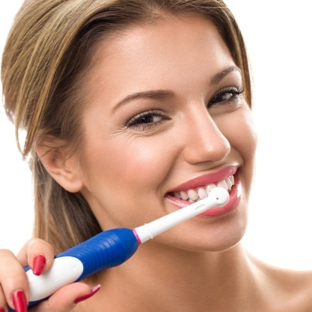 Woman performing at home dental hygiene routine