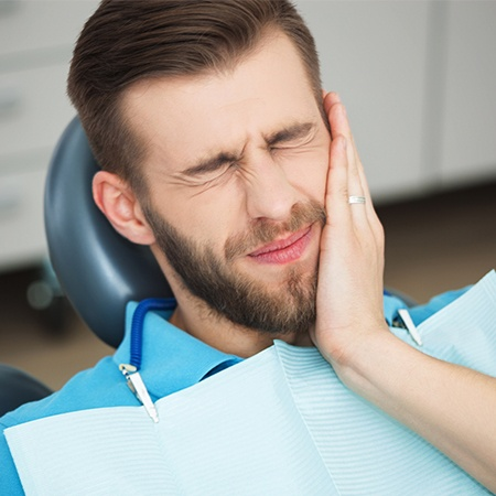 Man in need of root canal therapy holding jaw in pain
